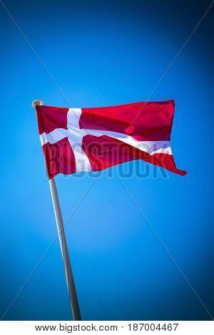 Denmark flag on sunny day against clear blue sky