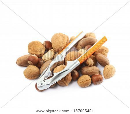 Pile of multiple different kind of nuts with the nutcracker over it, composition isolated over the white background