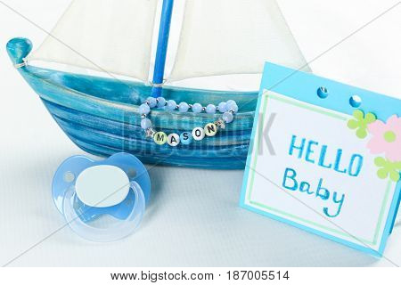 Composition with baby name bracelet on white fabric background