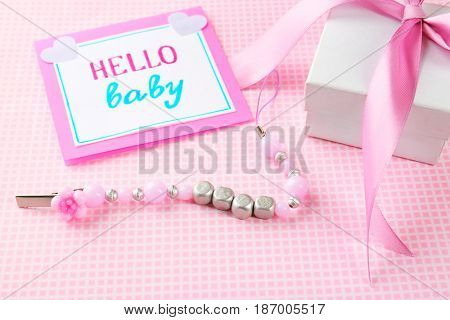 Pacifier clip with baby name, greeting card and gift box on table