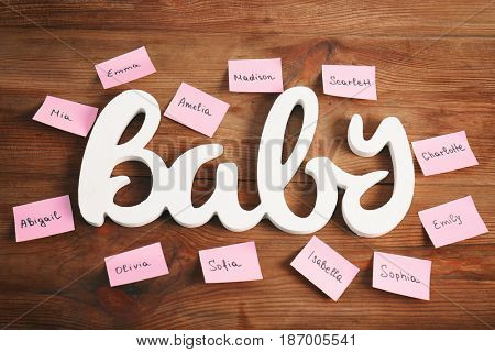 Word BABY and paper stickers with different names on wooden background