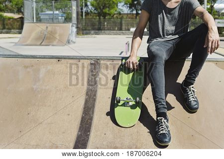 closeup of a young caucasian man with a skate board in his hand in an outdoors skate park