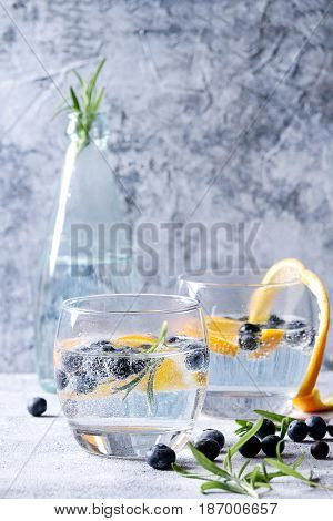 Tonic water cocktail with rosemary, blueberries and orange. Two cold glasses and bottle with zest and bubbles over gray blue texture background. Refreshing beverage alco non alcohol