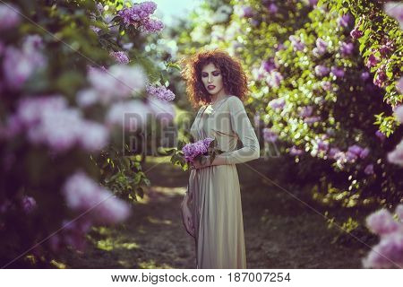 Young woman in alley of lilac bushes in the garden.