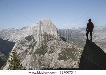 A young hiker is standing on a rock enjoying the view towards famous Half Dome at Glacier Point in beautiful golden evening light at sunset in summer Yosemite National Park California USA