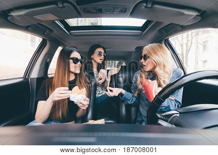 Three Young Women Drive A Car, Speaking Each Other And Eating A Fast Food In A Car In Traffic Jam