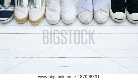 The shoes are placed on a white wooden floor.