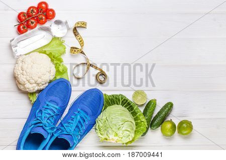 Fitness, active lifestyles Concept. Fresh healthy vegetables, sport shoes on white wood background. copy space for text. Top view