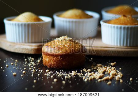 homemade muffin in porcelain form on a wooden board with crushed peanuts