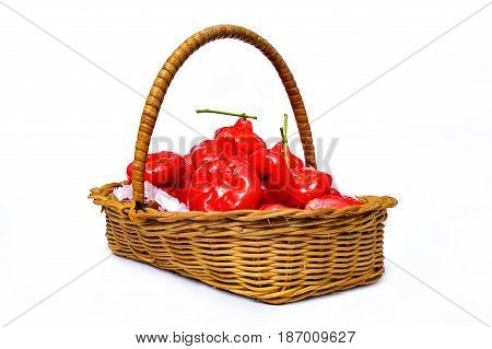 Rose apple red fruit in the wicker basket isolate on white background Rose apple or Chomphu-kaew in Thai, is a tropical fruit, originated in India. The fruit is bright red and combined into a bunch. It shaped like a bell upside down. It is small and sligh