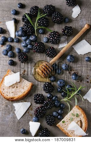 Berries blackberry and blueberry, honey on dipper, rosemary, sliced goat cheese with bread served over gray metal texture background. Summer sandwich. Top view