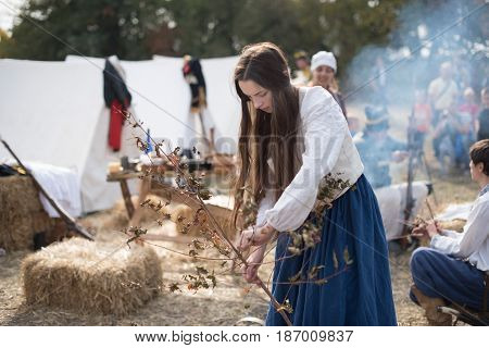01 October 2016. A historical reenactment of the Wars History in Kiev, Ukraine. An installation of Napoleon Army camp, a French laundress girl collecting brushwood.