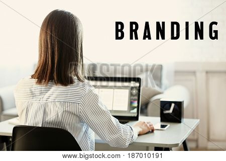 Brand marketing concept. Word BRANDING and woman working with laptop on background