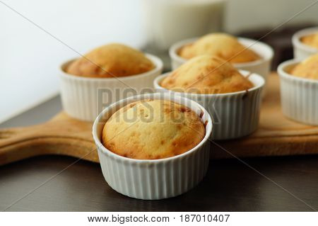 Homemade vanilla muffins in porcelain forms on a wooden board