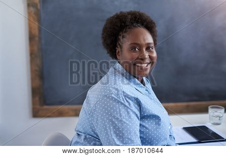 Portrait of a smiling young African businesswoman sitting at her desk while working alone in a large modern office