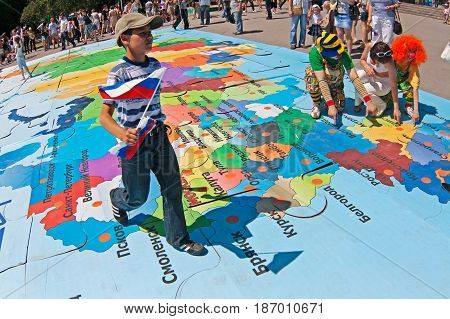 Volgograd Russia - June 12 2011: Boy with flag walks on a puzzle of map of Russia on the Independence day of Russia in Volgograd