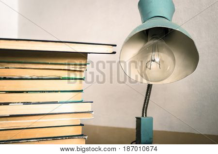Books and vintage blue lamp on a wooden table.
