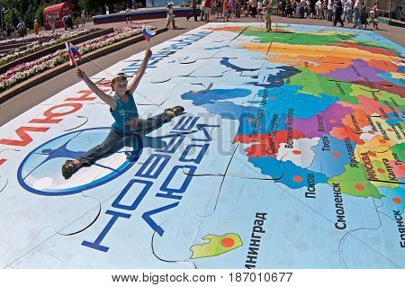 Volgograd Russia - June 12 2011: Boy with flags sits on a twine on a puzzle of map of Russia on the Independence day of Russia in Volgograd