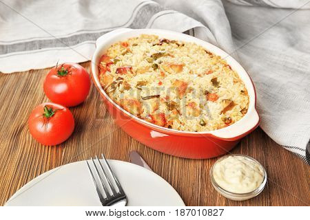 Tasty rice with chicken and vegetables in baking dish on kitchen table