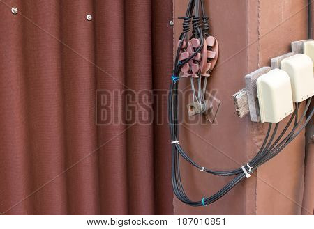 Drop wire clamp with telephone wire cable on red concrete wall with gypsum roof tile. Drop wire clamp concept.