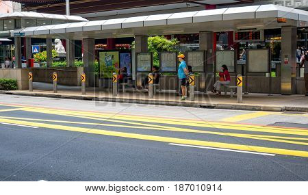 SINGAPORE - MAR 21 2017 : Local people and group tourist waiting for bus at bus stop at Orchard Rd Singapore on March 21 2017.