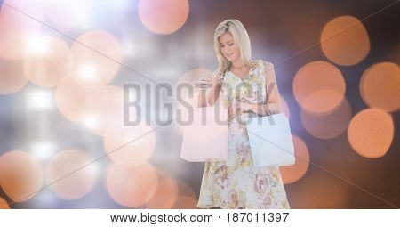 Digital composite of Young woman with shopping bags over bokeh