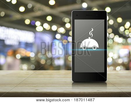 Restaurant cloche flat icon on modern smart phone screen on wooden table over blur light and shadow of shopping mall Food delivery concept