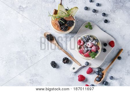 Various dessert breakfast layered chia seeds, chocolate pudding, rice porridge in glass decorated by fresh blackberries, sliced pear, cocoa powder. On serving board gray texture background. Flat lay