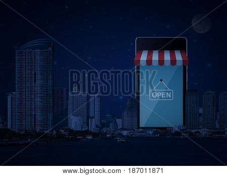 Modern smart mobile phone with on line shopping store sign modern office city tower river and fantasy night sky e-business concept