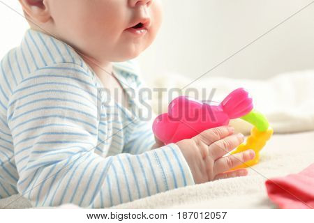 Cute baby holding toy rattle on bed, closeup