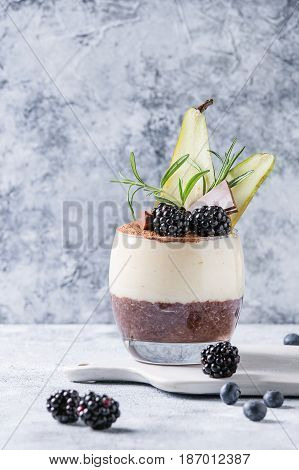 Dessert breakfast layered chia seeds, chocolate pudding, rice porridge in glass decorated by fresh blackberries, sliced pear, cocoa powder. Stand on white serving board over gray texture background.