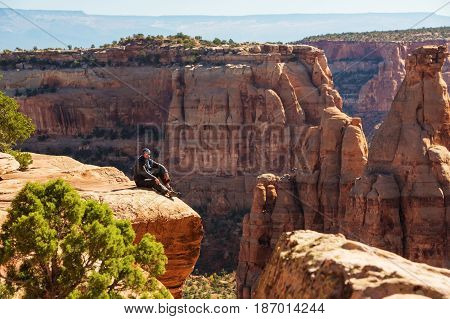 Hiker is sitting on the cliff in Colorado National monument USA