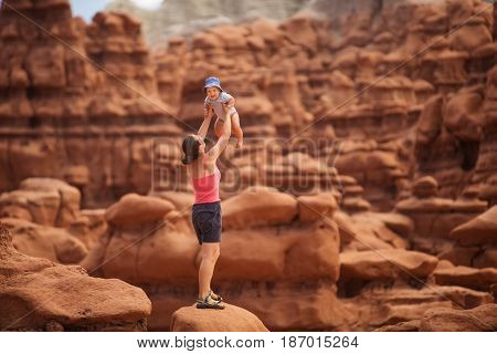 A mother and her baby son visit Goblin valley state park in Utah USA
