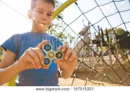 boy holds a spinner fidget in his hands. satisfied kid plays with a spinner on the playground. Blurred background.