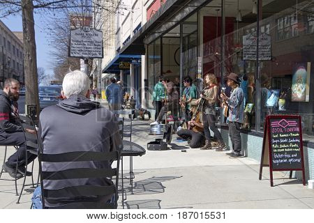 Asheville North Carolina USA - March 24, 2017: People sit at outdoors tables on the street as buskers play music for tips in front of the historic Woolworth Building and a man does push ups on the sidewalk nearby on a sunny day in downtown Asheville, NC