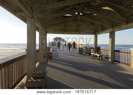 Clearwater Beach; Florida; USA - January 24, 2017: Sunset at Pier 60 on Clearwater Beach a 1080 foot fishing pier and recreational park with a bait house store telescopes and covered pavilions and a large beach playground.
