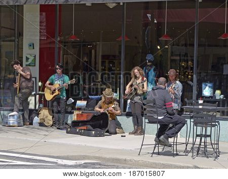 Asheville, North Carolina, USA - March 24, 2017: Buskers play music for tips on the street in front of the historic Woolworth Building as on a sunny day in downtown Asheville, NC