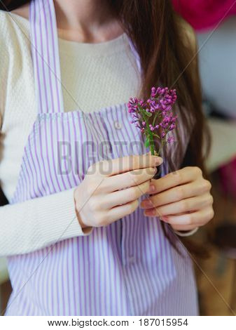Floristics hobby and work. Unrecognisible woman in striped apron holding a small brunch of lilac flower.