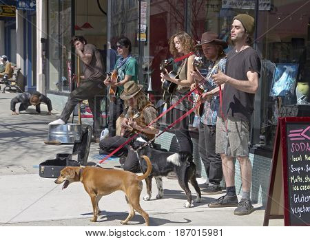 Asheville, North Carolina, USA - March 24, 2017: Buskers play music for tips on the street in front of the historic Woolworth Building as as a man does push ups on the sidewalk nearby on a sunny day in downtown Asheville, NC