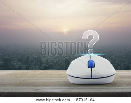 Question mark sign icon with wireless computer mouse on wooden table over modern city tower at sunset vintage style Customer support concept