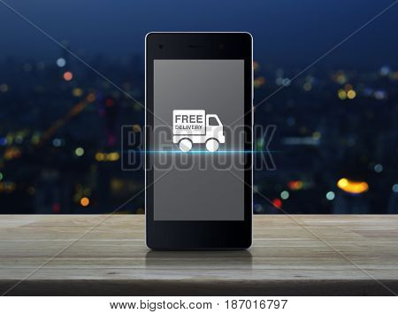 Free delivery truck icon on modern smart phone screen on wooden table over blur colorful night light of city tower Transportation business concept
