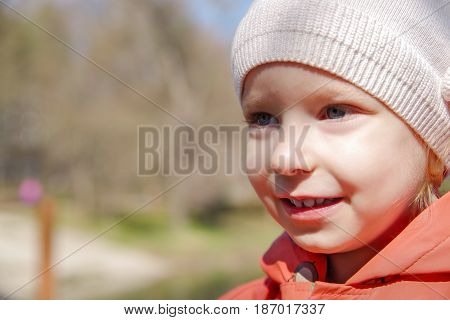 Little girl screaming aloud in the park on a nature background