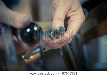 Process of wedding ring crafting. Close up of jeweler  using ring mandrel to measure the size of wedding ring
