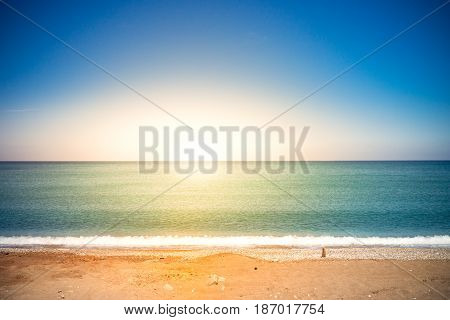 Calm blue sea and sky. Sunset on the beach. Travel background. Summer vacation holiday. Toned.