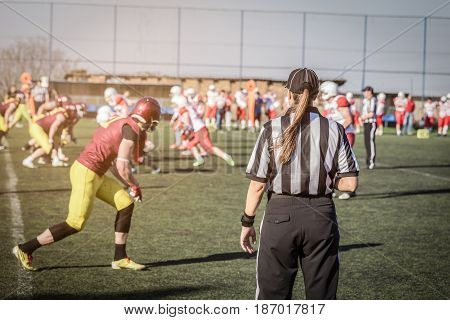 Female American football referee and blurred players in the background