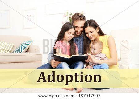 Adoption concept. Happy family reading book at home