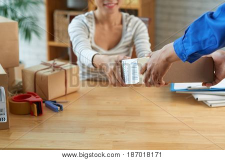 Hands of postman giving parcel to young smiling woman