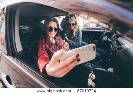 Group Of Girls Having Fun With The Car. Taking Selfie While Driving In Trip