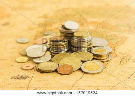 Close up heap of money gold coins on old world map treasure and wealth concepts.