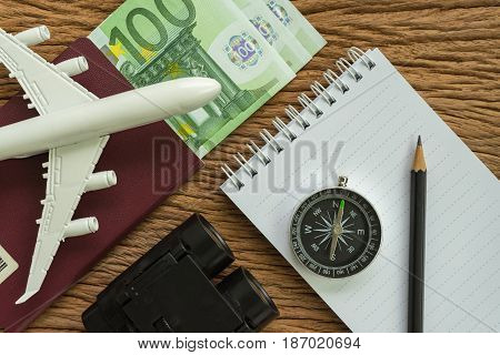Travel planning concept with airplane passport compass binoculars pencil paper note and Euro banknotes on wood table.